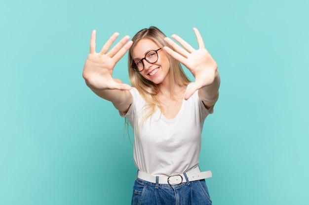 Młoda blond ładna kobieta uśmiecha się i wygląda przyjaźnie, pokazując numer dziesięć lub dziesiąty z ręką do przodu, odliczając w dół