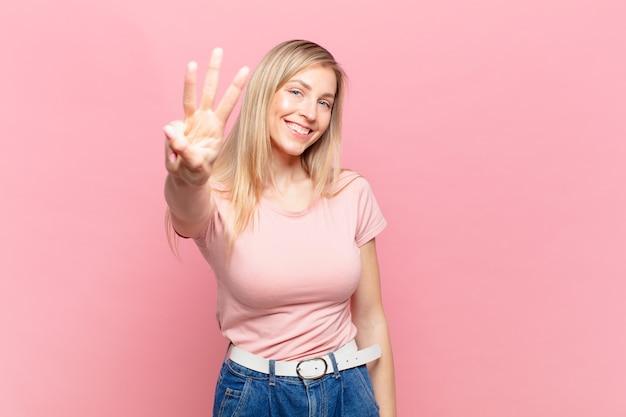 Młoda blond ładna kobieta uśmiecha się i wygląda przyjaźnie, pokazując numer trzy lub trzeci z ręką do przodu, odliczając w dół