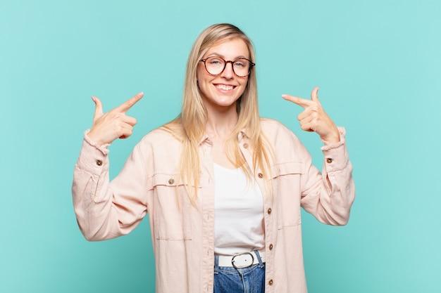 Młoda blond ładna kobieta uśmiecha się pewnie, wskazując na swój szeroki uśmiech, pozytywna, zrelaksowana, zadowolona postawa