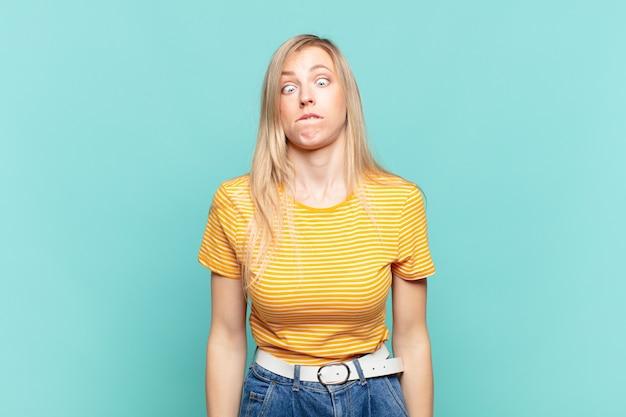Młoda blond ładna kobieta wygląda głupkowato i zabawnie z głupim zezowatym wyrazem twarzy, żartując i wygłupiając się