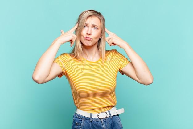 Młoda blond ładna kobieta wygląda na skoncentrowaną i intensywnie myśli o swoim pomyśle, wyobrażając sobie rozwiązanie wyzwania lub problemu