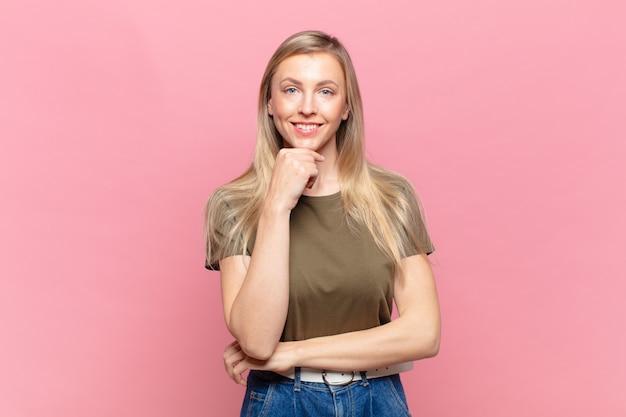 Młoda blond ładna kobieta wygląda na szczęśliwą i uśmiecha się z ręką na brodzie, zastanawia się lub zadaje pytanie, porównując opcje