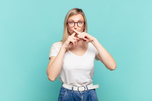 Młoda blond ładna kobieta wyglądająca na poważną i niezadowoloną z dwoma palcami skrzyżowanymi z przodu w odrzuceniu, prosząca o ciszę