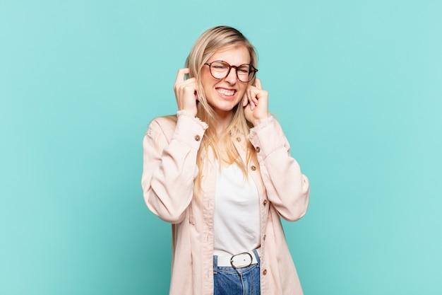 Młoda blond ładna kobieta wyglądająca na wściekłą, zestresowaną i zirytowaną, zakrywająca obydwa uszy ogłuszającym hałasem, dźwiękiem lub głośną muzyką