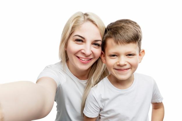 Młoda blond mama z synem w wieku 7 lat robi selfie. miłość i czułość. na białym tle na białej ścianie.