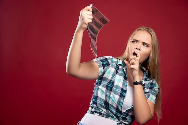 Młoda blond modelka sprawdza sceny z filmu polaroidowego i wygląda na niezadowoloną i przerażoną.