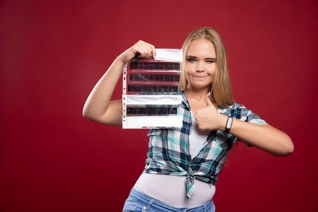 Młoda blond modelka sprawdza sceny z filmu polaroidowego i wygląda na zadowoloną.