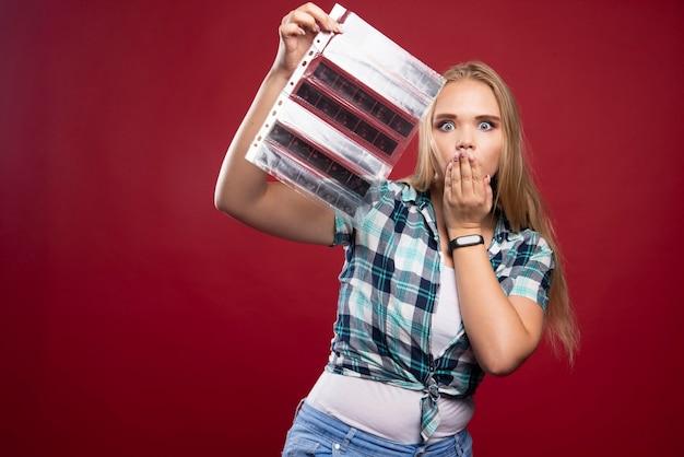 Młoda blond modelka sprawdza sceny z filmu polaroidowego i wygląda na zaskoczoną i rozczarowaną.