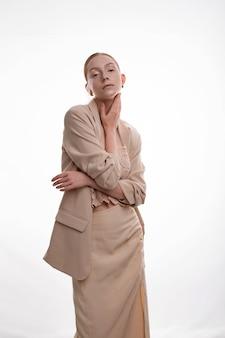 Młoda blond modelka z makijażem artystycznym pozowanie w beżowym kolorze spódnicy