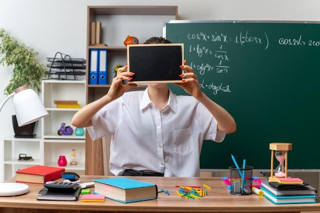 Młoda blond nauczycielka matematyki siedzi przy biurku z narzędziami szkolnymi i trzyma mini tablicę przed twarzą w klasie