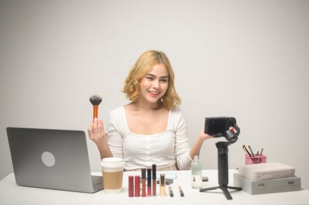 Młoda blond przedsiębiorczyni pracująca z laptopem prezentuje produkty kosmetyczne podczas transmisji online na żywo w studiu na białym tle, sprzedając koncepcję blogera internetowego i kosmetycznego