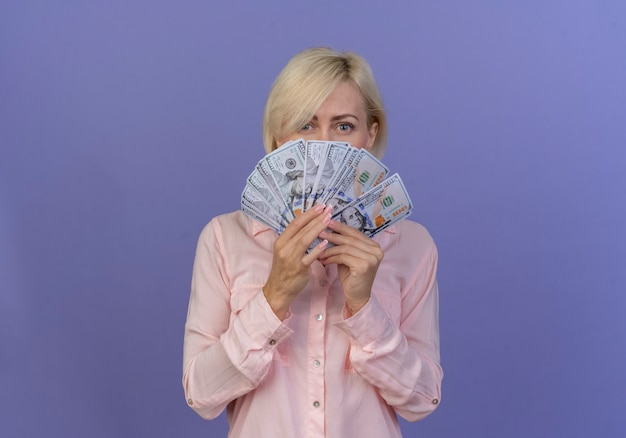 Młoda blond słowiańska kobieta trzyma pieniądze i patrząc na kamery zza pieniędzy na białym tle na fioletowym tle z miejsca na kopię