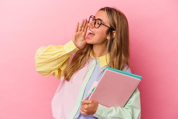 Młoda blond studentka kaukaski kobieta trzyma książki na białym tle, krzycząc i trzymając dłoń w pobliżu otwartych ust.