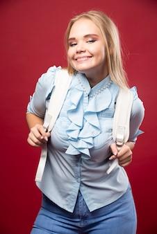 Młoda blond studentka z plecakiem wraca do szkoły i czuje się urocza i szczęśliwa.