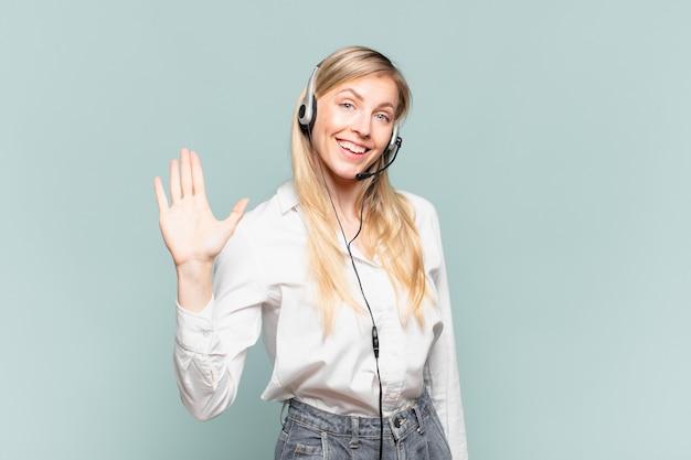 Młoda blond telemarketerka uśmiecha się radośnie i radośnie, machając ręką, witając cię i pozdrawiając lub żegnając się