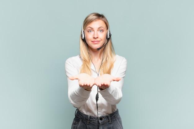 Młoda blond telemarketerka uśmiecha się radośnie z przyjaznym, pewnym siebie, pozytywnym spojrzeniem, oferując i pokazując przedmiot lub koncepcję