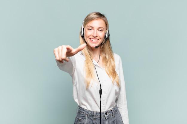 Młoda blond telemarketerka wskazująca na kamerę z zadowolonym, pewnym siebie, przyjaznym uśmiechem, wybierająca ciebie
