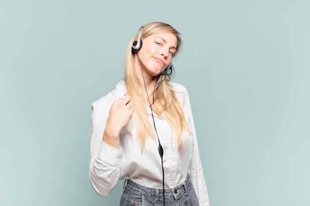 Młoda blond telemarketerka wygląda na arogancką, odnoszącą sukcesy, pozytywną i dumną, wskazując na siebie