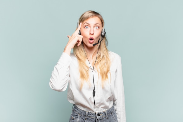 Młoda blond telemarketerka wygląda na zaskoczoną, z otwartymi ustami, zszokowaną, realizując nową myśl, pomysł lub koncepcję