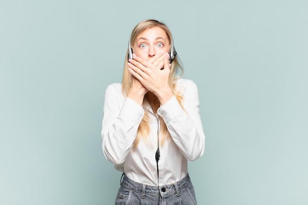 """Młoda blond telemarketerka zakrywająca usta dłońmi ze zszokowanym, zdziwionym wyrazem twarzy, zachowująca tajemnicę lub mówiąca """"ups"""""""