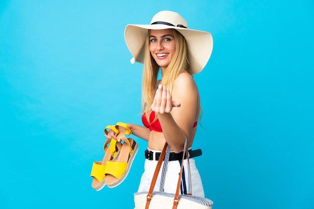 Młoda blond urugwajska kobieta w stroju kąpielowym w letnie wakacje trzyma torbę plażową i letnie sandały na na białym tle niebieskim, zapraszając do przyjścia z ręką. cieszę się, że przyszedłeś