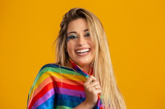 Młoda blond włosa kobieta w stroju ciesząca się karnawałowym przyjęciem pokrytym koszulką lgbt. sam. jeden. flaga lgbt. symbol lgbt +.