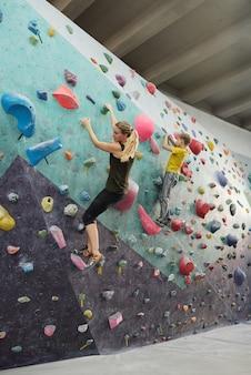 Młoda blondynka aktywna kobieta i jej syn w sportowej ścianie wspinaczkowej z małymi sztucznymi skałami podczas treningu w czasie wolnym