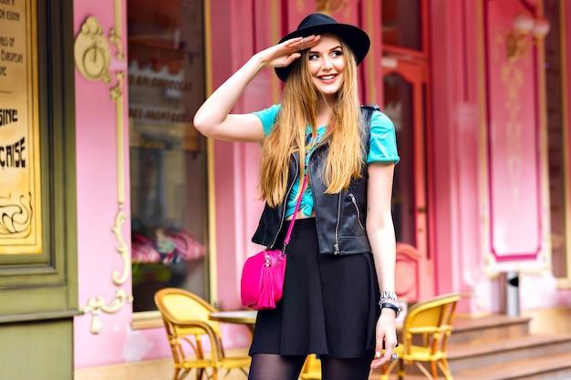 Młoda blondynka bawi się na wakacjach w europie, stylowy, jasny strój hipster, pozuje w pobliżu francuskiej restauracji, niesamowite długie włosy, ładna twarz, moda uliczna.