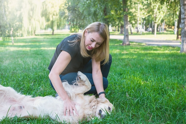 Młoda blondynka bawi się psem golden retrievera w parku