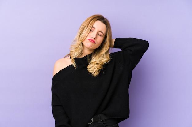 Młoda blondynka cierpi na ból szyi z powodu siedzącego trybu życia.