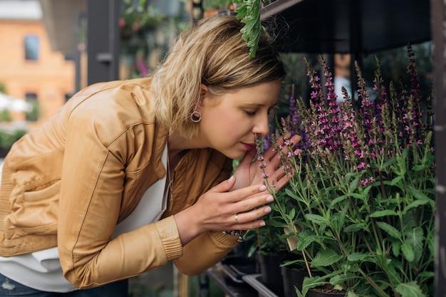 Młoda blondynka czerpie ogromną przyjemność z aromatu kwitnących ziół w kwiaciarni. praca kwiaciarni. aromaterapia. zioła lecznicze i rośliny. kawałek natury w mieście. styl życia.