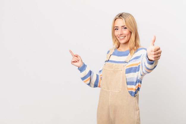 Młoda blondynka czuje się dumna, uśmiechając się pozytywnie z kciukami w górę