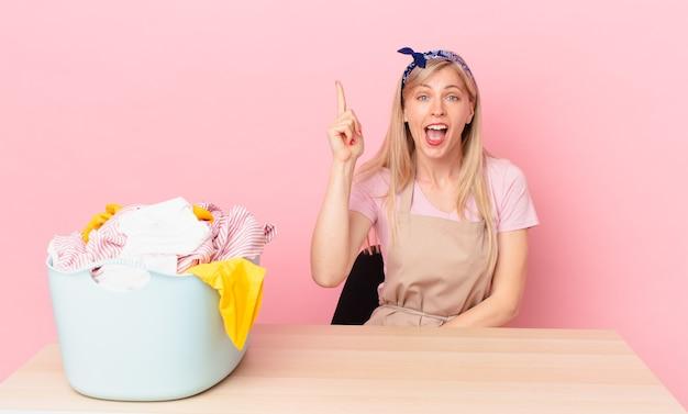 Młoda blondynka czuje się jak szczęśliwy i podekscytowany geniusz po zrealizowaniu pomysłu. koncepcja prania ubrań