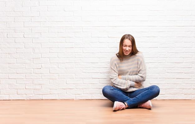 Młoda blondynka czuje się niespokojna, chora, chora i nieszczęśliwa, cierpi na bolesny ból brzucha lub grypę siedzącą na podłodze