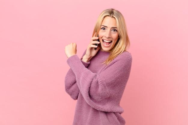Młoda blondynka czuje się szczęśliwa i staje przed wyzwaniem lub świętuje i rozmawia ze smartfonem