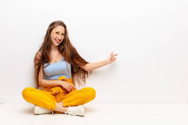 Młoda blondynka czuje się szczęśliwa i wesoła, uśmiecha się i wita, zapraszając przyjaznym gestem siedząc na podłodze