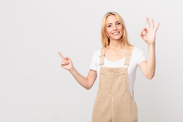 Młoda blondynka czuje się szczęśliwa, okazując aprobatę dobrym gestem