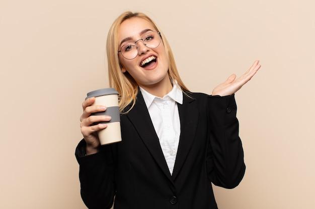 Młoda blondynka czuje się szczęśliwa, zdumiona, szczęśliwa i zaskoczona, świętując zwycięstwo obiema rękami w górze