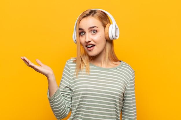 Młoda blondynka czuje się szczęśliwa, zdziwiona i wesoła, uśmiecha się pozytywnie, realizuje rozwiązanie lub pomysł