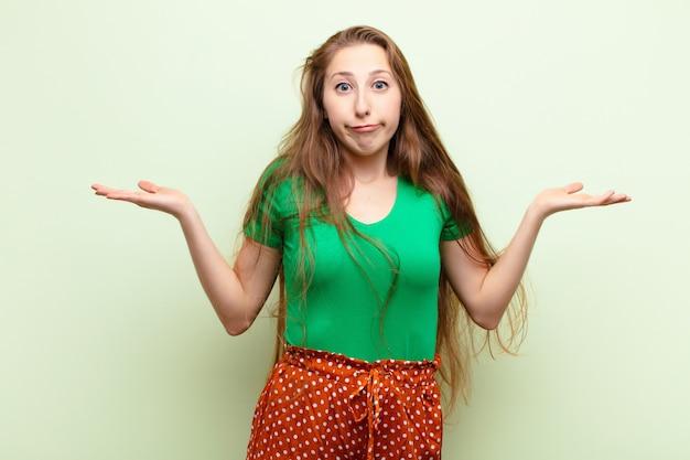 Młoda blondynka czuje się zdziwiona i zdezorientowana, wątpi, waży lub wybiera różne opcje z zabawnym wyrazem twarzy