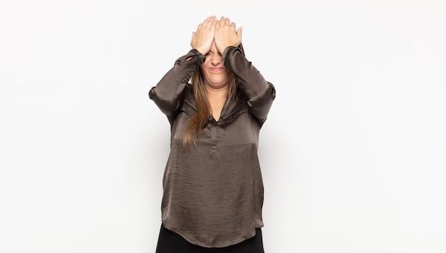 Młoda blondynka czuje się zestresowana i niespokojna, przygnębiona i sfrustrowana bólem głowy, podnosząc obie ręce do głowy
