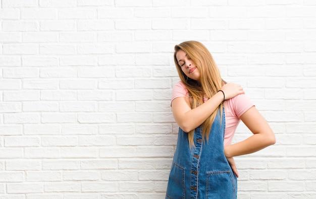 Młoda blondynka czuje się zmęczona, zestresowana, niespokojna, sfrustrowana i przygnębiona, cierpi z powodu bólu pleców lub szyi na ścianę