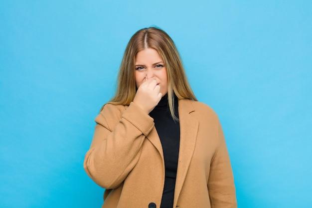 Młoda blondynka czuje się zniesmaczona, trzymając nos, aby nie poczuć nieprzyjemnego i nieprzyjemnego smrodu na ścianie