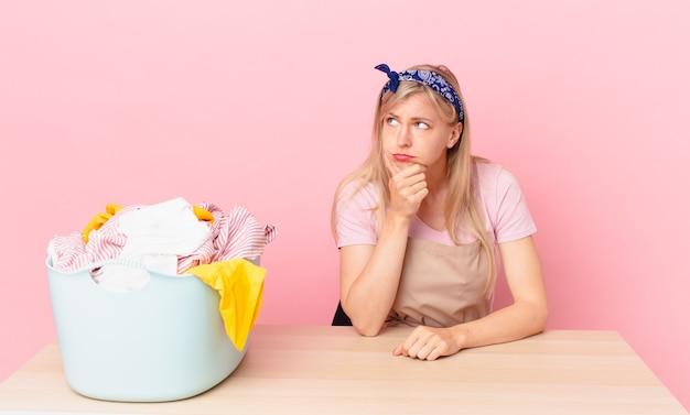 Młoda blondynka czuje się znudzona, sfrustrowana i senna po męczącym dniu. koncepcja prania ubrań