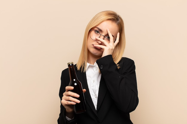 Młoda blondynka czuje się znudzona, sfrustrowana i senna po męczącym, nudnym i żmudnym zadaniu, trzymając twarz ręką