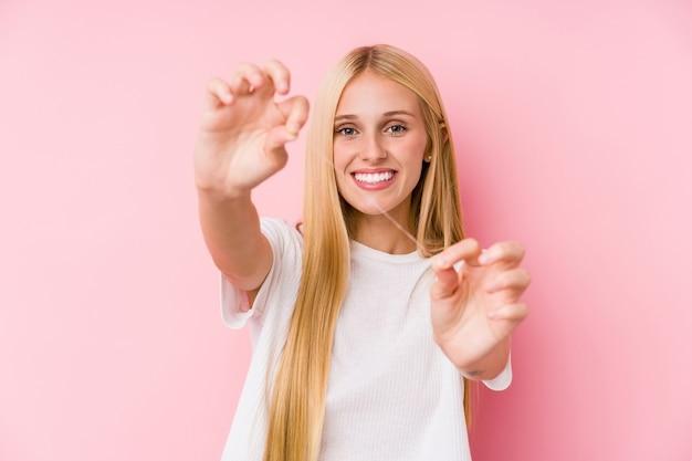 Młoda blondynka czyści zęby nicią dentystyczną