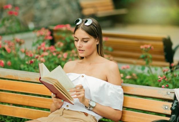 Młoda blondynka czyta książkę z entuzjazmem, siedząc na ławce w parku