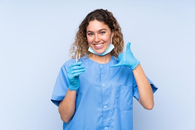 Młoda blondynka dentysta kobieta trzyma narzędzia na białym tle na niebieskiej ścianie dokonywanie gestu telefonu