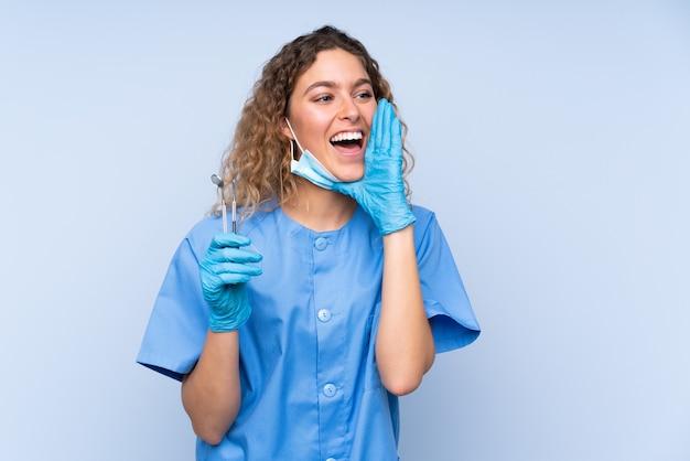 Młoda blondynka dentysta kobieta trzyma narzędzia na białym tle na niebieskiej ścianie krzycząc z szeroko otwartymi ustami