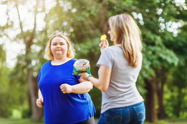 Młoda blondynka dużych rozmiarów biegnie po parku obok kobiety jedzącej frytki